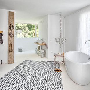 Diseño de cuarto de baño principal, mediterráneo, grande, con bañera exenta, paredes blancas, lavabo sobreencimera, encimera de madera, suelo blanco y encimeras beige
