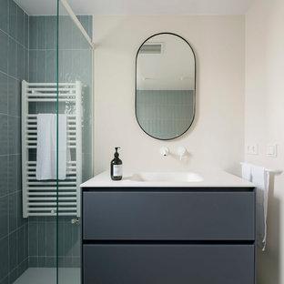 Diseño de cuarto de baño con ducha, escandinavo, de tamaño medio, con armarios con paneles lisos, puertas de armario grises, baldosas y/o azulejos grises, paredes beige, lavabo integrado, suelo gris y encimeras blancas