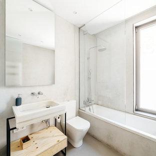 Foto de cuarto de baño con ducha, actual, con armarios tipo mueble, puertas de armario de madera clara, bañera encastrada, combinación de ducha y bañera, paredes blancas, lavabo suspendido, suelo gris y ducha abierta