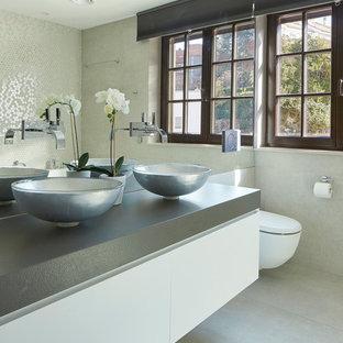 Modelo de cuarto de baño contemporáneo con armarios con paneles lisos, puertas de armario blancas, lavabo sobreencimera, suelo gris, encimeras grises y paredes grises
