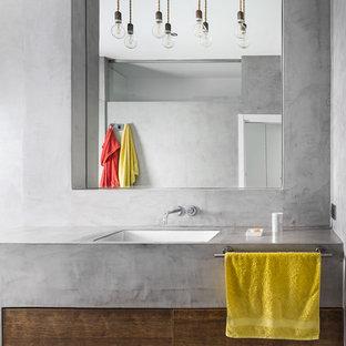 Diseño de cuarto de baño contemporáneo con armarios con paneles lisos, puertas de armario de madera en tonos medios, paredes grises, lavabo bajoencimera, suelo gris y encimeras grises