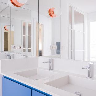 Foto de cuarto de baño principal, contemporáneo, grande, con puertas de armario azules, ducha a ras de suelo, sanitario de pared, paredes blancas, suelo de bambú, lavabo integrado, encimera de cuarzo compacto, suelo marrón y armarios con paneles lisos