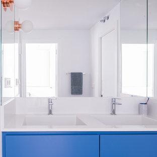 Ejemplo de cuarto de baño principal, nórdico, grande, con armarios tipo mueble, puertas de armario azules, ducha a ras de suelo, sanitario de pared, paredes blancas, suelo de bambú, lavabo integrado, encimera de cuarzo compacto y suelo marrón
