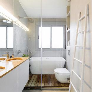 Modelo de cuarto de baño principal, nórdico, pequeño, con armarios con paneles lisos, puertas de armario blancas, bañera exenta, sanitario de pared, paredes grises, lavabo bajoencimera, suelo gris, ducha con puerta con bisagras y encimeras naranjas