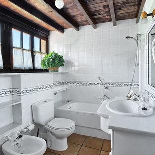 Diseño de cuarto de baño principal, rural, de tamaño medio, con armarios con paneles lisos, bidé, baldosas y/o azulejos blancos, baldosas y/o azulejos de cerámica, paredes blancas, suelo de baldosas de terracota y lavabo bajoencimera