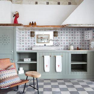 Modelo de cuarto de baño mediterráneo, de tamaño medio, con puertas de armario verdes, suelo de baldosas de cerámica, suelo multicolor, armarios con puertas mallorquinas y paredes blancas