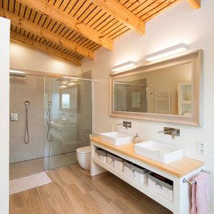 バルセロナの地中海スタイルのおしゃれな浴室 (オープンシェルフ、白いキャビネット、バリアフリー、グレーのタイル、白い壁、淡色無垢フローリング、ベッセル式洗面器、木製洗面台、ベージュの床、引戸のシャワー、ベージュのカウンター、板張り壁、造り付け洗面台、洗面台2つ) の写真