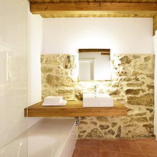 Immagine di una stanza da bagno mediterranea con vasca ad alcova, vasca/doccia, pareti bianche, lavabo a bacinella, top in legno e pavimento rosso