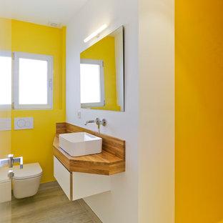 Ejemplo de cuarto de baño actual con sanitario de pared, paredes amarillas, lavabo sobreencimera, armarios con paneles lisos, puertas de armario blancas, suelo de madera clara y encimera de madera