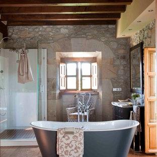 Modelo de cuarto de baño mediterráneo con bañera exenta, ducha esquinera, suelo de madera en tonos medios, suelo marrón y ducha con puerta con bisagras