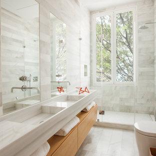 Imagen de cuarto de baño con ducha, actual, de tamaño medio, con armarios con paneles lisos, puertas de armario de madera oscura, sanitario de una pieza, ducha empotrada, baldosas y/o azulejos grises, baldosas y/o azulejos de piedra, paredes grises, suelo de travertino, encimera de cuarcita y lavabo integrado