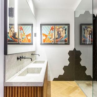 Imagen de cuarto de baño contemporáneo con armarios tipo mueble, puertas de armario de madera oscura, ducha a ras de suelo, baldosas y/o azulejos negros, paredes blancas, suelo de madera clara, lavabo integrado, suelo beige, ducha abierta y encimeras grises