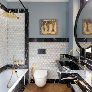 Modelo de cuarto de baño con ducha, contemporáneo, con bañera encastrada, combinación de ducha y bañera, sanitario de pared, baldosas y/o azulejos blancas y negros, baldosas y/o azulejos blancos, baldosas y/o azulejos en mosaico, paredes grises, suelo de madera en tonos medios, lavabo integrado, encimera de mármol, suelo marrón, ducha con cortina y encimeras negras