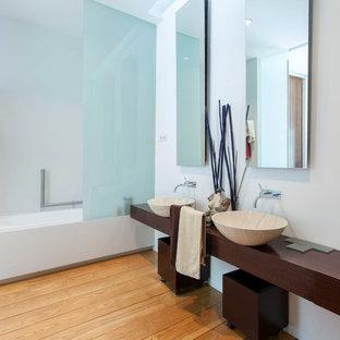 Foto de cuarto de baño actual con combinación de ducha y bañera, paredes blancas, suelo de madera en tonos medios, lavabo sobreencimera, encimera de madera, suelo marrón y encimeras marrones