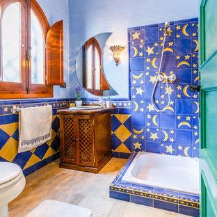 Foto de cuarto de baño con ducha, mediterráneo, con puertas de armario de madera oscura, ducha abierta, baldosas y/o azulejos azules, baldosas y/o azulejos amarillos, paredes azules, lavabo encastrado y ducha abierta