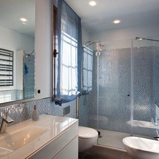 Diseño de cuarto de baño con ducha, contemporáneo, con armarios con paneles lisos, puertas de armario blancas, ducha empotrada, sanitario de pared, baldosas y/o azulejos azules, paredes azules, lavabo tipo consola, suelo gris y ducha con puerta con bisagras
