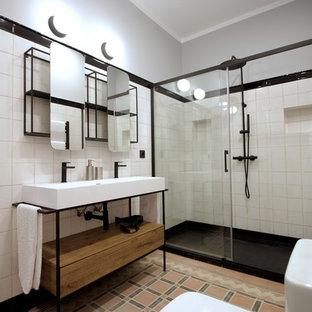 Diseño de cuarto de baño tradicional renovado con armarios abiertos, puertas de armario de madera oscura, ducha a ras de suelo, lavabo integrado, ducha con puerta corredera, baldosas y/o azulejos blancos, paredes grises y encimeras blancas