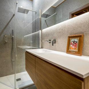 Diseño de cuarto de baño con ducha, actual, de tamaño medio, con armarios con paneles lisos, puertas de armario de madera oscura, ducha empotrada, lavabo integrado, baldosas y/o azulejos grises, paredes grises, suelo gris y encimeras blancas