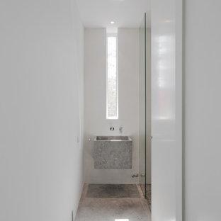 Foto de cuarto de baño con ducha, moderno, pequeño, con puertas de armario grises, paredes blancas, lavabo suspendido, suelo gris y encimeras grises