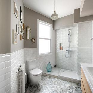 Diseño de cuarto de baño con ducha, actual, de tamaño medio, con armarios con paneles lisos, puertas de armario de madera clara, ducha empotrada, sanitario de dos piezas, baldosas y/o azulejos blancos, baldosas y/o azulejos de cemento, paredes grises, lavabo integrado, suelo multicolor y ducha abierta