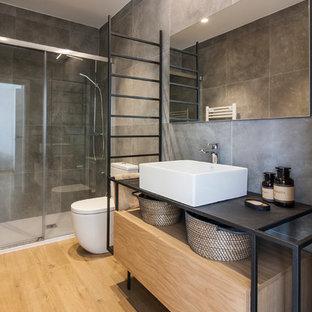 Идея дизайна: главная ванная комната в современном стиле с серой плиткой, керамогранитной плиткой, настольной раковиной, столешницей из нержавеющей стали и душем с раздвижными дверями