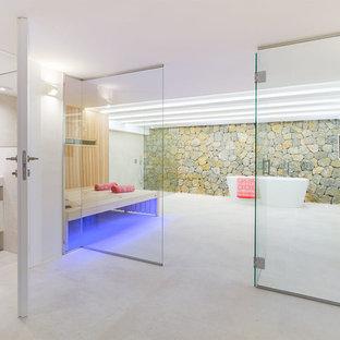 Diseño de sauna actual con puertas de armario blancas, bañera exenta, paredes blancas, lavabo integrado, suelo beige y encimeras blancas