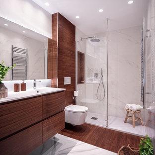 Modelo de cuarto de baño con ducha, contemporáneo, con armarios con paneles lisos, puertas de armario de madera oscura, ducha empotrada, sanitario de pared, paredes blancas, lavabo integrado, suelo multicolor y encimeras blancas
