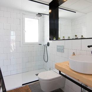 Foto de cuarto de baño con ducha, costero, con ducha empotrada, sanitario de pared, baldosas y/o azulejos blancos, paredes blancas, suelo de cemento, lavabo sobreencimera, encimera de madera, suelo gris, ducha abierta y encimeras beige