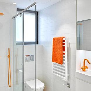 Ejemplo de cuarto de baño con ducha, marinero, pequeño, con armarios con paneles lisos, puertas de armario blancas, ducha esquinera, sanitario de pared, baldosas y/o azulejos blancos, baldosas y/o azulejos de cerámica, paredes blancas, lavabo integrado y ducha con puerta corredera