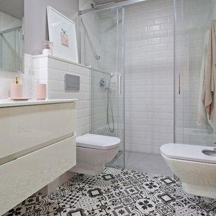 Modelo de cuarto de baño con ducha, contemporáneo, de tamaño medio, con ducha a ras de suelo, sanitario de pared, baldosas y/o azulejos blancos, baldosas y/o azulejos de cemento, paredes grises, suelo con mosaicos de baldosas, lavabo integrado, ducha con puerta corredera, armarios con paneles lisos, puertas de armario blancas y encimeras blancas