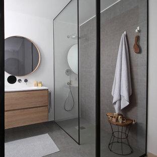 Imagen de cuarto de baño principal, moderno, de tamaño medio, con armarios con paneles lisos, puertas de armario de madera oscura, ducha abierta, sanitario de pared, baldosas y/o azulejos grises, paredes blancas, suelo gris, encimeras blancas y lavabo tipo consola