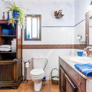 Diseño de cuarto de baño mediterráneo con armarios con puertas mallorquinas, puertas de armario marrones, sanitario de dos piezas, baldosas y/o azulejos de cerámica, paredes multicolor, lavabo encastrado, suelo marrón y encimeras beige