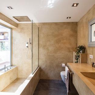 Esempio di una stanza da bagno con doccia minimal di medie dimensioni con vasca ad alcova, vasca/doccia, WC sospeso, pareti beige, pavimento in cemento, lavabo rettangolare, doccia aperta, nessun'anta, ante beige e pavimento grigio