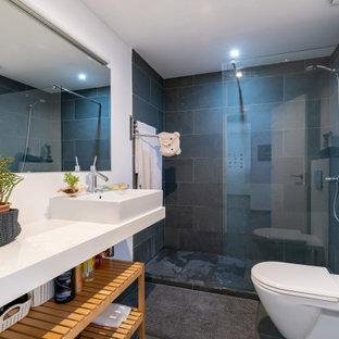 Modelo de cuarto de baño con ducha, actual, de tamaño medio, con armarios abiertos, puertas de armario blancas, ducha empotrada, sanitario de pared, baldosas y/o azulejos grises, paredes blancas, suelo de baldosas de porcelana, lavabo sobreencimera, suelo negro y encimeras blancas
