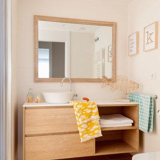 Foto de cuarto de baño actual con armarios con paneles lisos, puertas de armario de madera oscura, paredes beige, lavabo sobreencimera, suelo marrón y encimeras blancas