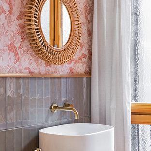 Modelo de cuarto de baño costero con armarios abiertos, baldosas y/o azulejos grises, paredes rosas, lavabo sobreencimera, encimera de madera y encimeras marrones