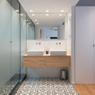 Diseño de cuarto de baño principal, actual, de tamaño medio, con armarios con paneles lisos, puertas de armario beige, ducha empotrada, paredes blancas, lavabo sobreencimera, encimera de madera, suelo multicolor, ducha con puerta con bisagras y encimeras beige