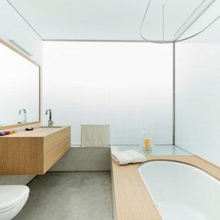 Foto di una stanza da bagno minimal di medie dimensioni con doccia a filo pavimento, WC sospeso, piastrelle bianche, lastra di vetro, pareti bianche, pavimento in cemento, lavabo da incasso, top in legno, vasca sottopiano e top marrone