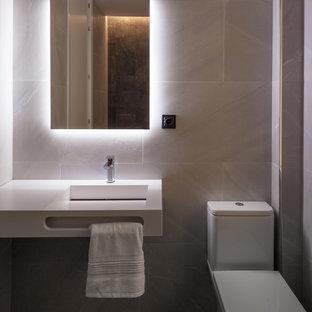 Foto de cuarto de baño con ducha, actual, con baldosas y/o azulejos grises, paredes grises, lavabo suspendido y encimeras blancas