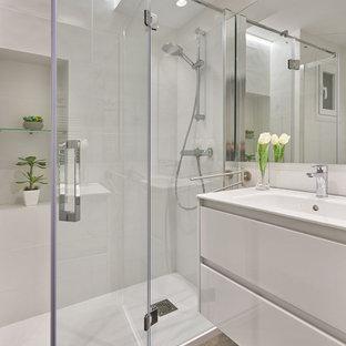 Foto de cuarto de baño con ducha, actual, de tamaño medio, con encimeras blancas, armarios con paneles lisos, puertas de armario blancas, ducha empotrada, baldosas y/o azulejos blancos, baldosas y/o azulejos de porcelana, paredes blancas, suelo de baldosas de porcelana, lavabo integrado, suelo gris y ducha con puerta con bisagras