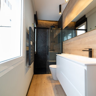 Immagine di una stanza da bagno con doccia minimal con ante lisce, ante bianche, doccia alcova, WC monopezzo, piastrelle nere, piastrelle di ciottoli, pareti grigie, parquet chiaro, lavabo integrato, pavimento beige, porta doccia scorrevole e top bianco
