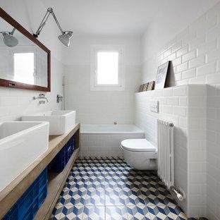 Foto de cuarto de baño ecléctico, de tamaño medio, con bañera empotrada, sanitario de una pieza, baldosas y/o azulejos blancos, baldosas y/o azulejos de cemento, paredes blancas, suelo de baldosas de cerámica, lavabo sobreencimera y encimera de cemento