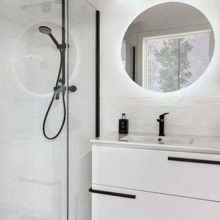 Idéer för små minimalistiska vitt badrum med dusch, med möbel-liknande, vita skåp, en kantlös dusch, en toalettstol med hel cisternkåpa, vit kakel, keramikplattor, vita väggar, klinkergolv i keramik, ett integrerad handfat, bänkskiva i kvarts, blått golv och dusch med gångjärnsdörr
