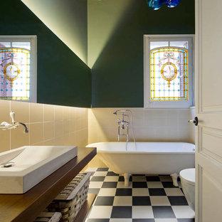 Diseño de cuarto de baño principal, bohemio, grande, con armarios abiertos, bañera con patas, suelo de baldosas de cerámica, lavabo sobreencimera, suelo multicolor, combinación de ducha y bañera, baldosas y/o azulejos beige, ducha abierta, puertas de armario de madera en tonos medios, paredes verdes y encimera de madera