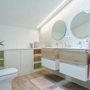 Ejemplo de cuarto de baño infantil, actual, con armarios con paneles lisos, puertas de armario de madera clara, sanitario de dos piezas, baldosas y/o azulejos blancos, paredes blancas, suelo de madera clara, lavabo encastrado, suelo beige y encimeras blancas