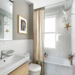 マドリードの小さいエクレクティックスタイルのおしゃれなマスターバスルーム (フラットパネル扉のキャビネット、淡色木目調キャビネット、アルコーブ型浴槽、シャワー付き浴槽、分離型トイレ、白いタイル、サブウェイタイル、グレーの壁、セラミックタイルの床、横長型シンク、マルチカラーの床、シャワーカーテン) の写真