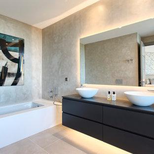 Modelo de cuarto de baño contemporáneo con armarios con paneles lisos, puertas de armario negras, bañera encastrada sin remate, paredes beige, lavabo sobreencimera y suelo gris