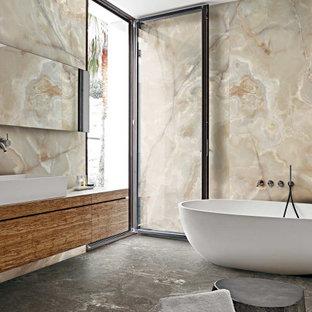 Imagen de cuarto de baño principal, actual, grande, con suelo de baldosas de cerámica, armarios con paneles lisos, puertas de armario de madera oscura, bañera exenta, baldosas y/o azulejos beige, lavabo sobreencimera, suelo gris y encimeras marrones