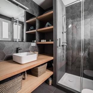 Ejemplo de cuarto de baño con ducha, actual, con armarios abiertos, puertas de armario de madera clara, ducha empotrada, baldosas y/o azulejos negros, baldosas y/o azulejos grises, suelo de pizarra, lavabo sobreencimera, encimera de madera, suelo negro y ducha con puerta corredera