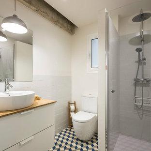Imagen de cuarto de baño principal, contemporáneo, de tamaño medio, con armarios tipo mueble, puertas de armario blancas, ducha empotrada, sanitario de una pieza, baldosas y/o azulejos blancos, baldosas y/o azulejos de cemento, paredes blancas, suelo con mosaicos de baldosas, lavabo sobreencimera, encimera de madera, suelo multicolor y ducha con puerta con bisagras